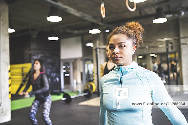 Junge Frau mit Trainingspartnern beim Training im Fitnessstudio