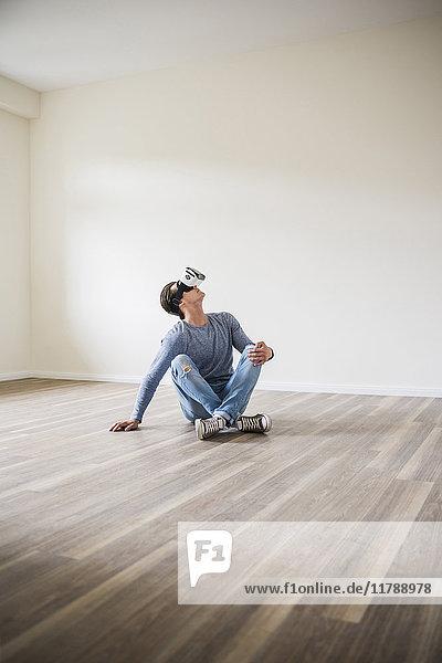 Mann in leerer Wohnung mit VR-Brille