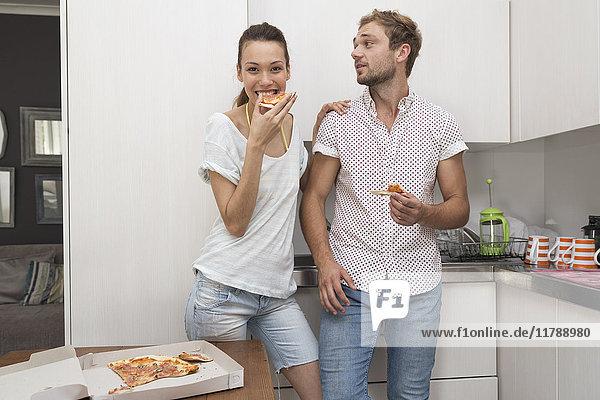 Junges Paar beim Pizzaessen in der Küche