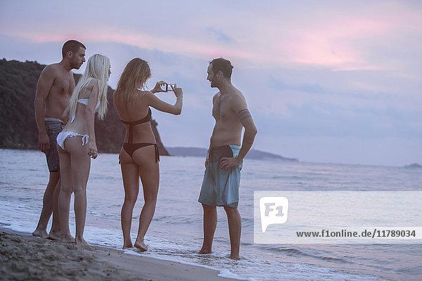 Vier Freunde am Strand beim Fotografieren bei Sonnenuntergang