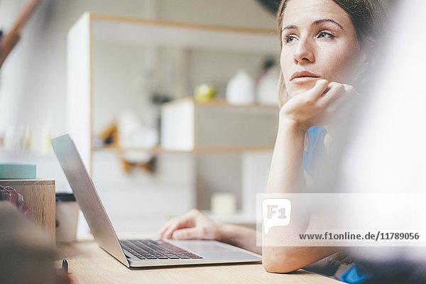 Junge Frau mit Laptop am Schreibtisch zu Hause