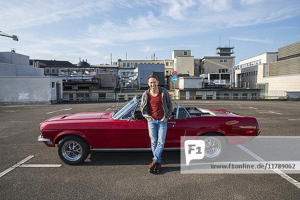 Porträt eines lächelnden  reifen Mannes  der sich gegen seinen geparkten Sportwagen lehnt.