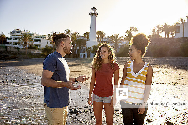 Spanien  Kanarische Inseln  Gran Canaria  drei Freunde  die gemeinsam am Strand entspannen