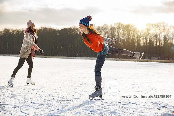 Zwei Frauen Schlittschuhlaufen auf dem zugefrorenen See