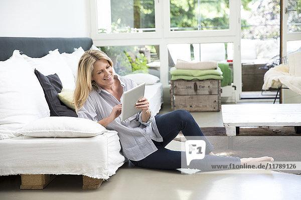 Entspannte Frau sitzend auf dem Boden des Wohnzimmers mit Tablette