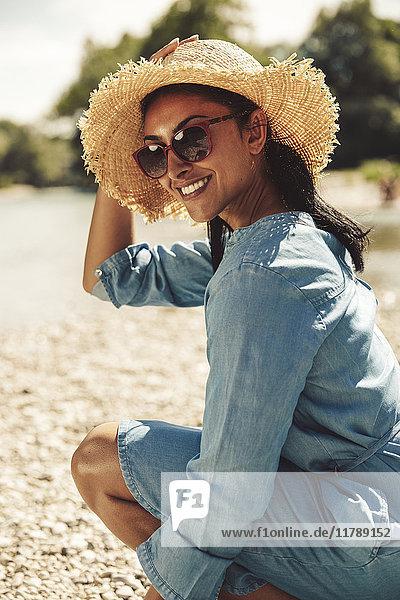 Porträt einer glücklichen Frau mit Strohhut und Sonnenbrille am Strand