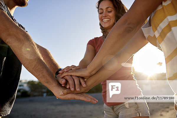 Drei Freunde  die sich am Strand die Hände reichen.