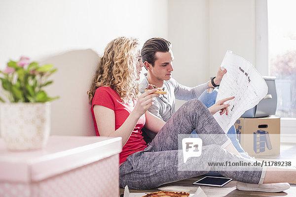 Junges Paar im neuen Zuhause sitzt auf dem Boden und bespricht den Grundriss.