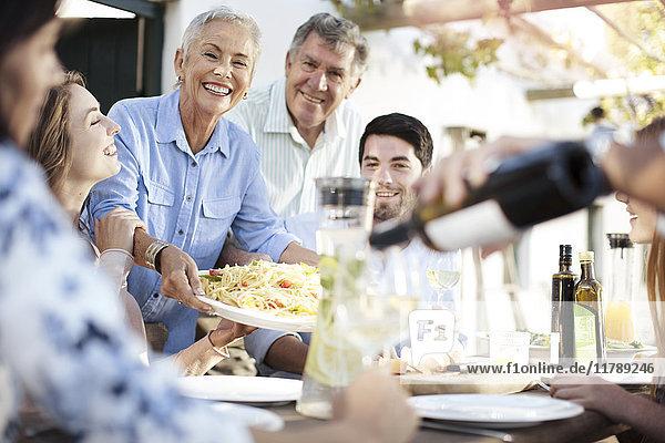 Glückliche Familie beim gemeinsamen Mittagessen im Freien