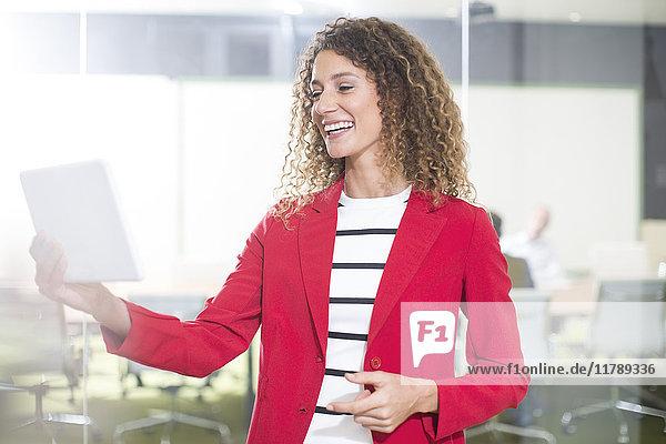 Glückliche Geschäftsfrau mit Tablette im Büro