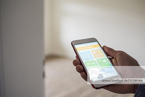 Mann zu Hause mit Smartphone und Smart Home Apps