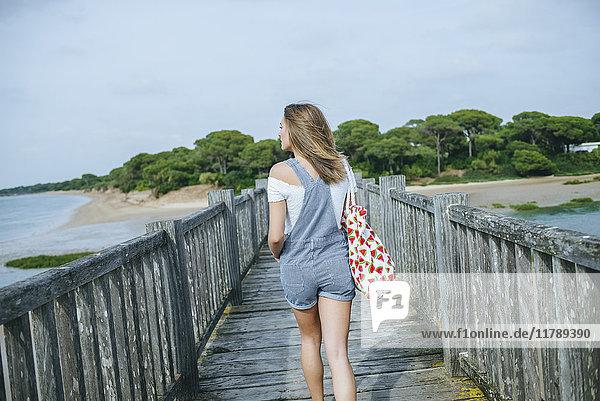 Rückansicht der Frau  die an der Strandpromenade zum Strand geht.