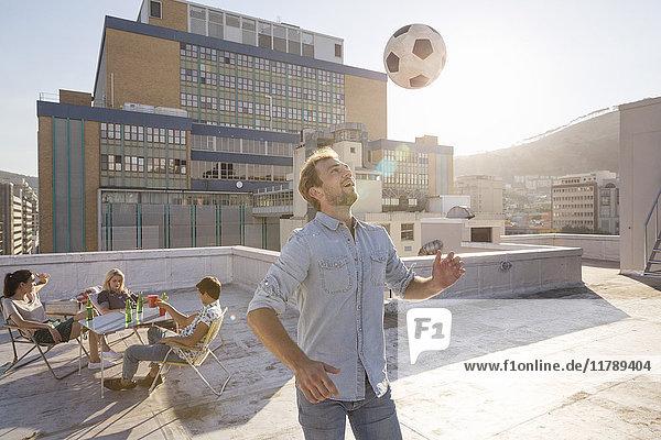Treffen der Freunde auf der Dachterrasse im Sommer  Fußball spielen