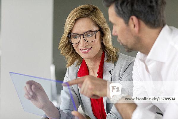 Geschäftsmann und Geschäftsfrau mit futuristischem tragbarem Gerät