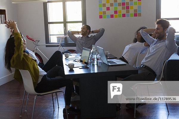 Geschäftsleute  die sich während eines Meetings im Büro zurücklehnen