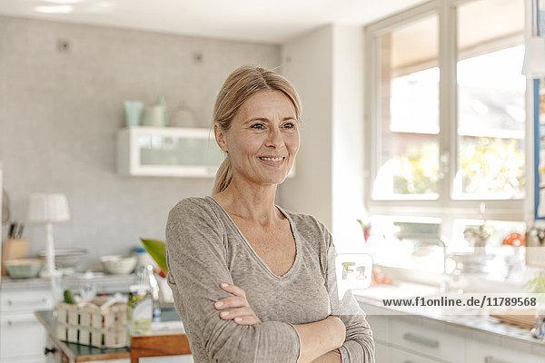 Porträt der lächelnden Frau zu Hause in der Küche