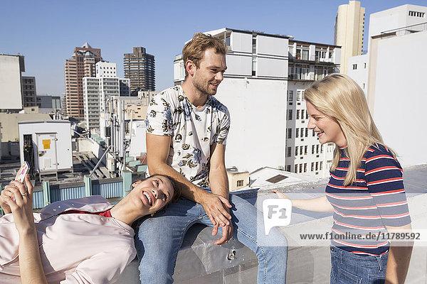Freunde treffen sich im Sommer auf einer Dachterrasse  Frau mit Smartphone