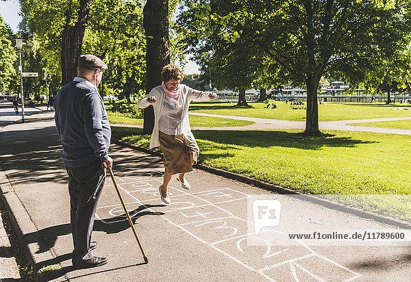Seniorin spielt Hopscotch  während ihr Mann sie beobachtet.