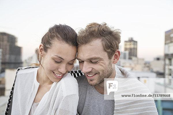 Romantisches Paar sitzt auf der Dachterrasse und genießt die Aussicht.