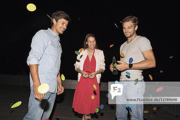 Junge Leute feiern eine Dachparty, schmeißen Konfetti.