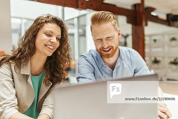 Geschäftsmann und Frau mit Laptop im Büro