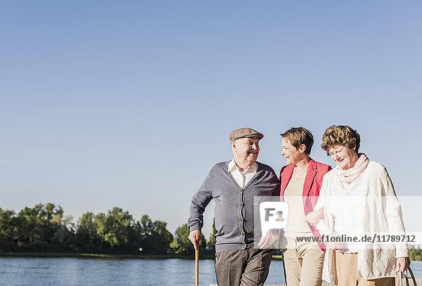 Eltern  die mit ihrer erwachsenen Tochter am Flussufer spazieren gehen.