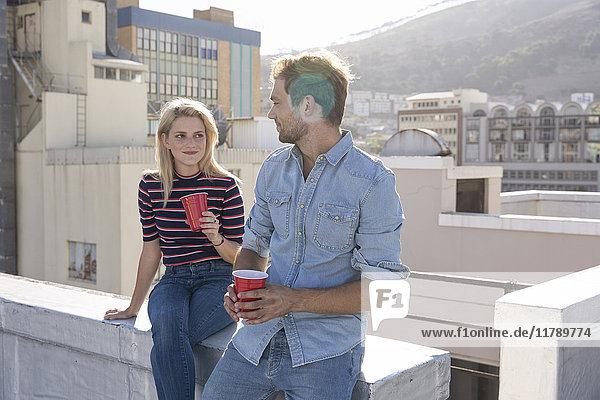 Freunde bei einem Drink auf der Dachterrasse