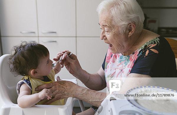 Großmutter füttert Baby in der Küche