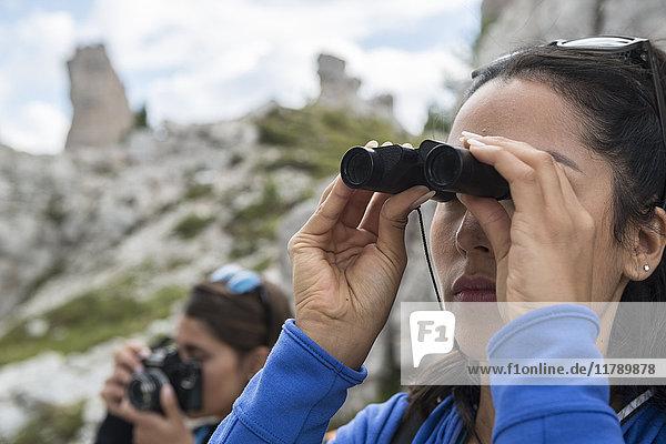 Italien  Dolomiten  Frau beobachtet die Natur mit dem Fernglas