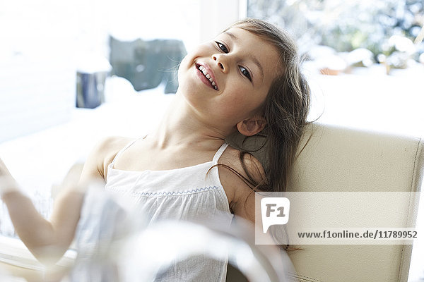 Portrait of smiling little girl on chair