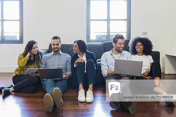 Porträt von glücklichen Kollegen auf der Couch mit Laptops