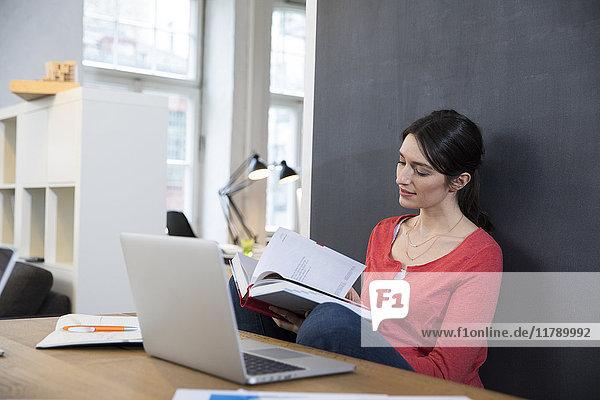 Frau mit Buch und Laptop am Schreibtisch im Büro