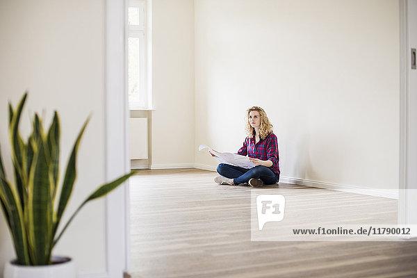 Junge Frau im neuen Zuhause sitzend auf dem Boden mit Plan