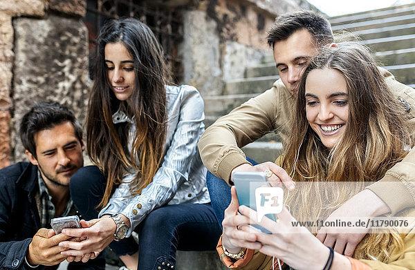 Gruppe von Freunden  die Nachrichten mit dem Smartphone senden
