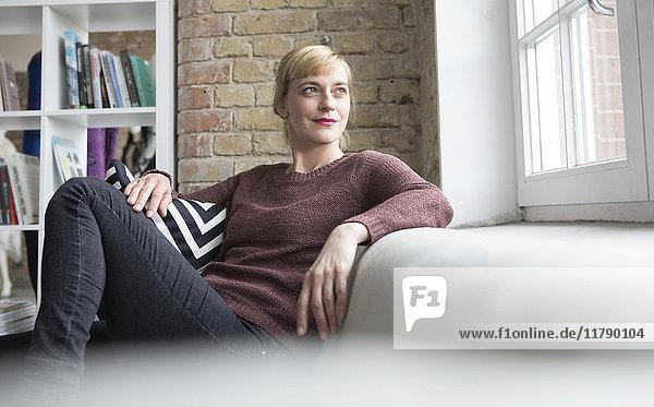 Frau entspannt auf der Couch zu Hause