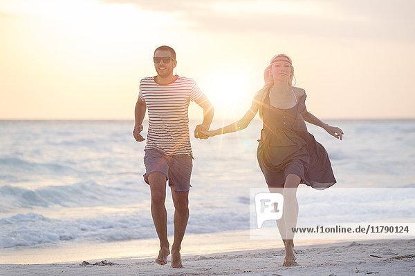 Ein junges Paar  das am Strand rennt und Händchen hält.