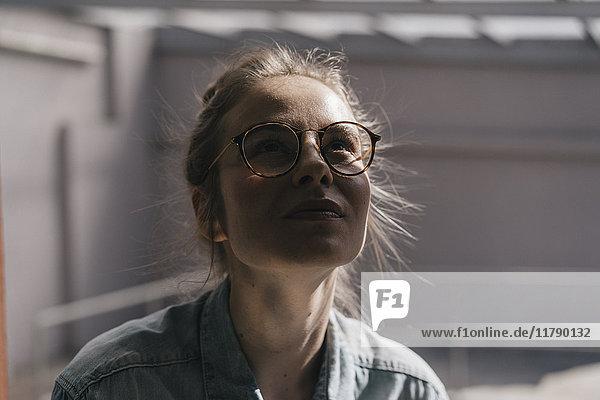 Junge Frau mit Brille  die nach oben schaut