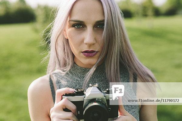 Junge Frau beim Fotografieren mit der Kamera in der Natur