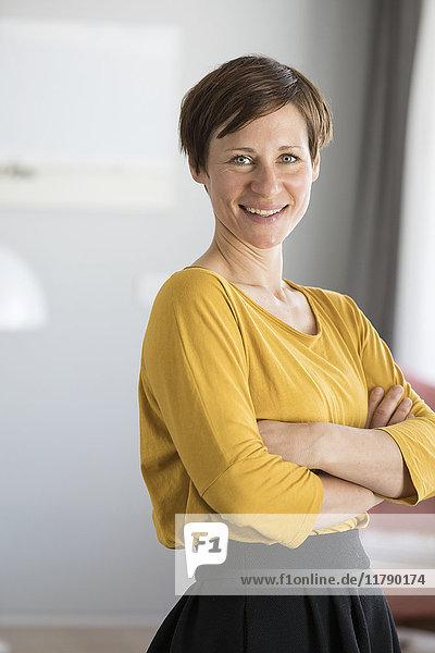 Porträt einer lächelnden Frau im gelben Sweatshirt