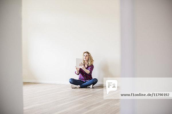 Junge Frau im neuen Zuhause sitzend auf dem Boden mit Tablette
