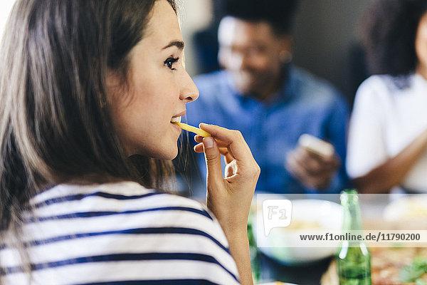 Frau isst Pommes Frites mit Freunden im Hintergrund