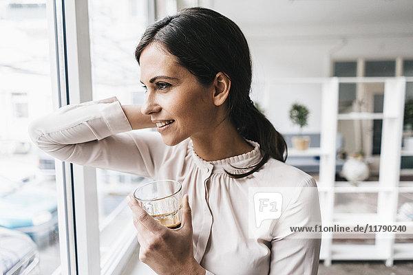 Lächelnde Frau hält Glas und schaut aus dem Fenster.