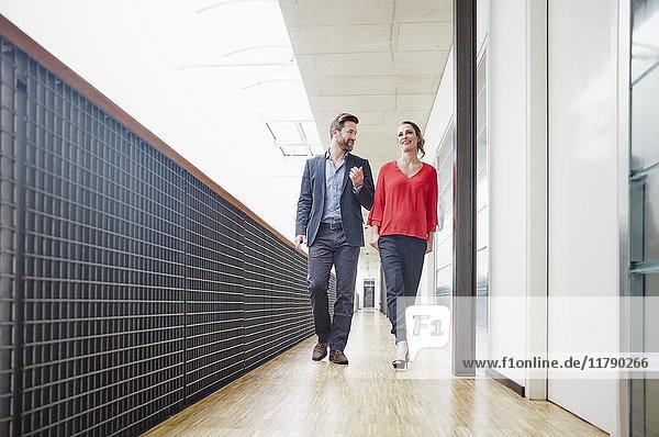 Geschäftsmann und Geschäftsfrau gehen auf Büroetage