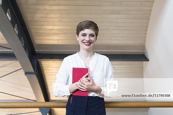 Porträt einer lächelnden Geschäftsfrau mit Notizbuch