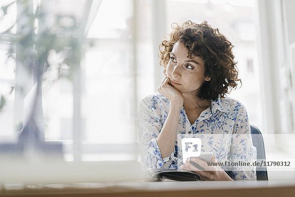 Geschäftsfrau im Büro mit Smartphone und Tagebuch  die besorgt aussieht.