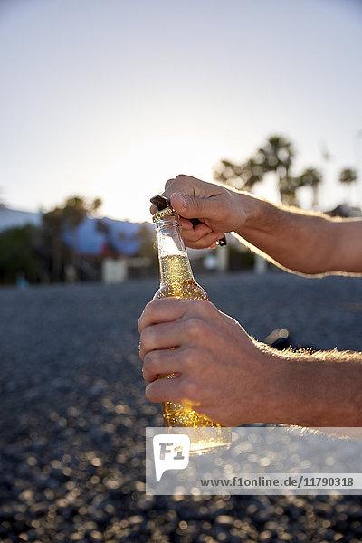 Männerhände öffnen Bierflasche am Strand