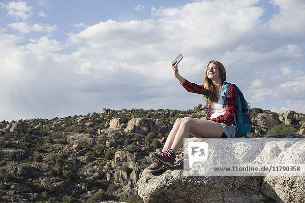Spanien  Madrid  junge Frau  die sich auf einem Felsen ausruht und während eines Trekking-Tages einen Selfie nimmt