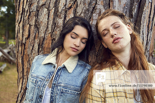 Porträt zweier junger Frauen  die sich mit geschlossenen Augen an den Baumstamm lehnen.