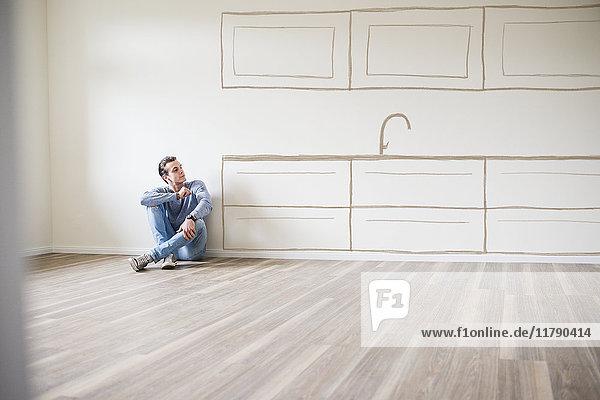 Junger Mann im neuen Zuhause sitzt auf dem Boden und denkt über Innenarchitektur nach.