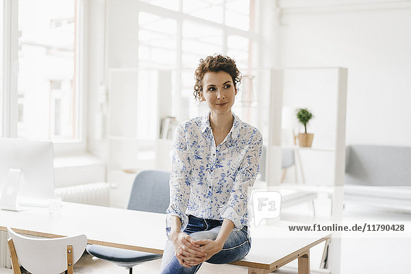 Geschäftsfrau im Büro sitzt auf dem Schreibtisch und sieht selbstbewusst aus.